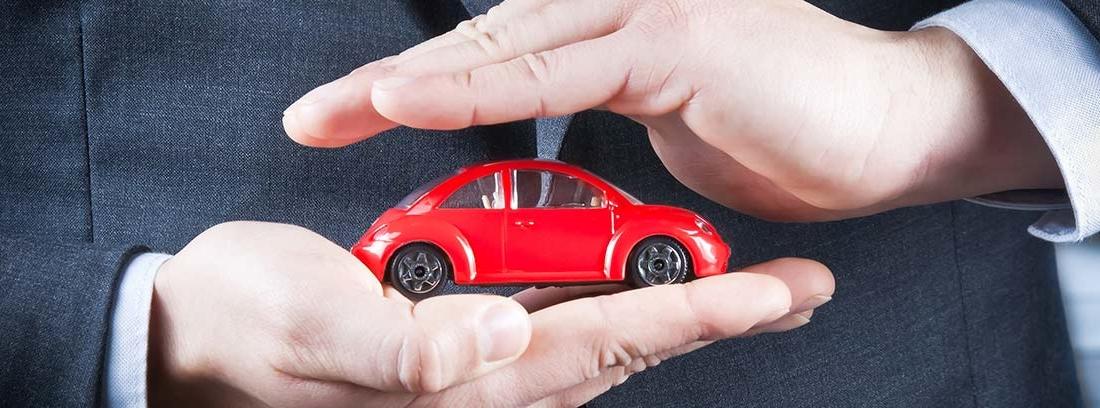 Miniatura de coche rojo entre las manos de un hombre.