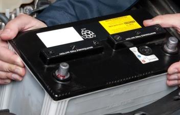 Manos sacan una batería de un coche.