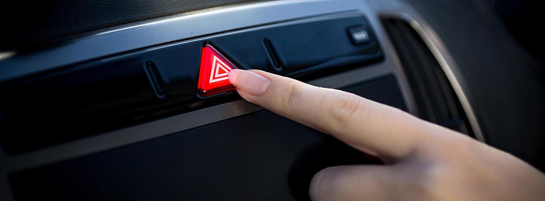 Mano apretando el botón de luces de emergencia dentro de un coche