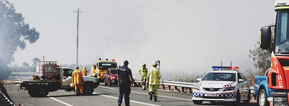 Carretera con coches se policía, bomberos y personal de emergencia.