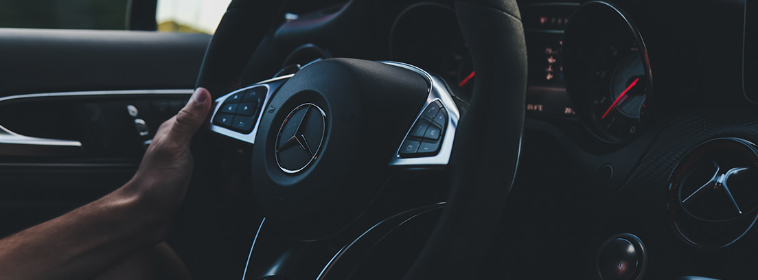 Mano sobre volante de coche.