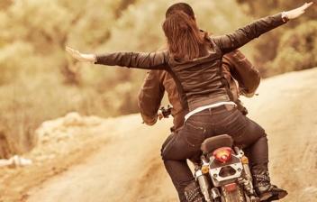 Hombre y mujer de espaldas circulando por una carretera con una moto