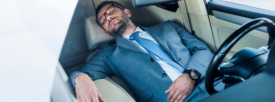 Hombre con traje durmiendo en el interior de su coche