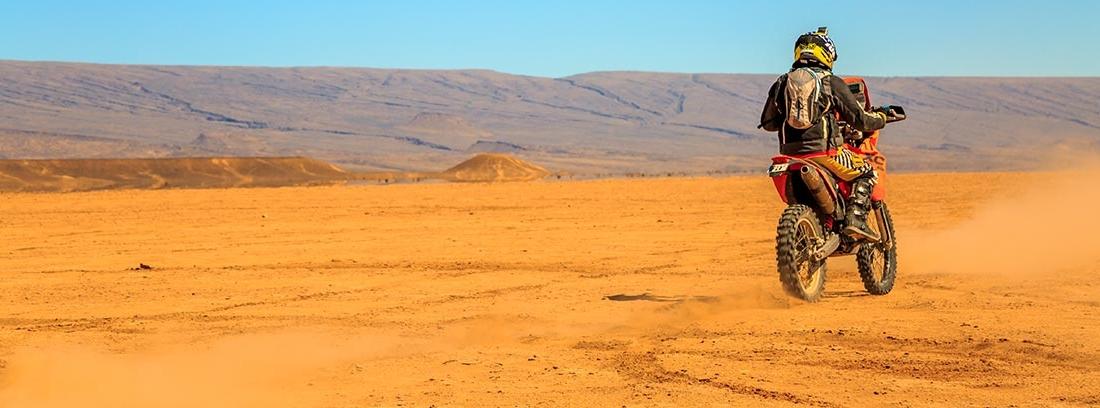 Piloto de espaldas circulando con su moto por el desierto