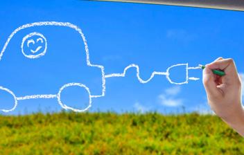 Mano dibujando en la ventanilla de un coche un coche eléctrico