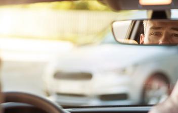 Hombre ajustando el espejo retrovisor de su coche