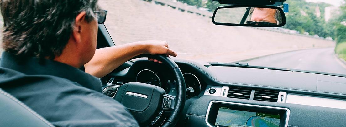 Hombre de espaladas dentro de un coche con una mano sobre el volante.