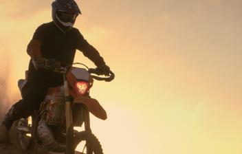 Piloto de Enduro sobre una duna al anochecer