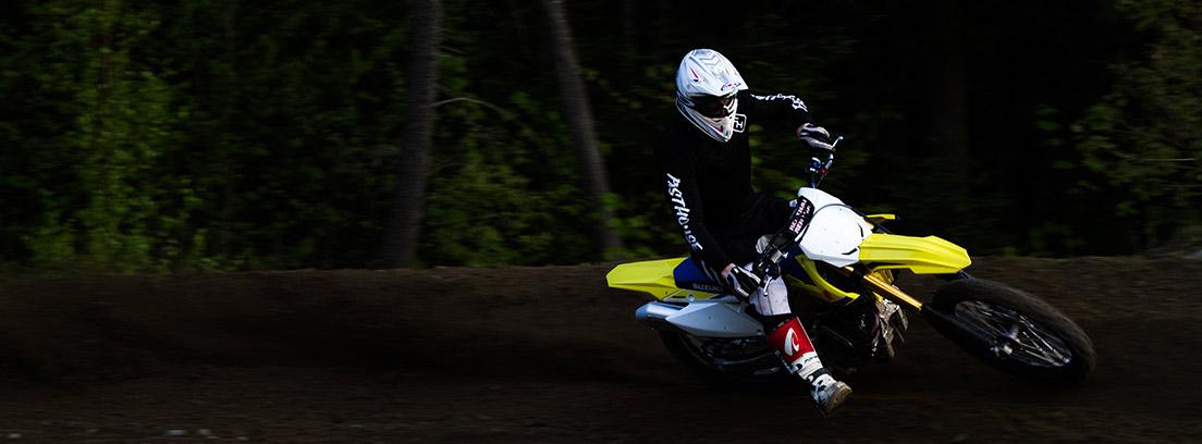 Motorista en moto de cross amarilla tomando curva sobre arena.