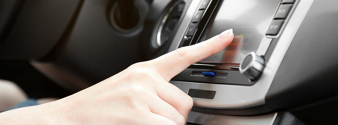Dedo sobre una pantalla multimedia dentro de coche.