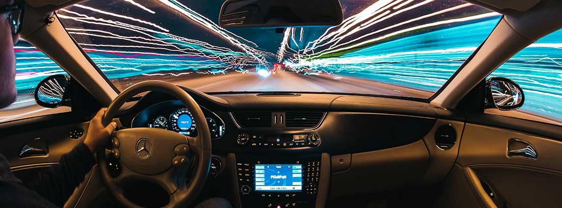 interior de coche con pantalla central iluminada y conductor sentado