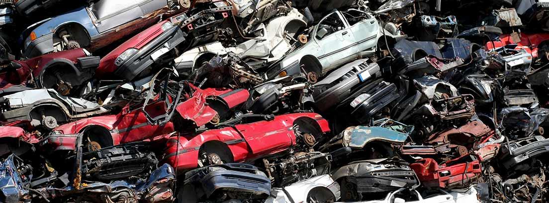 Varios coches apilados en un desguace