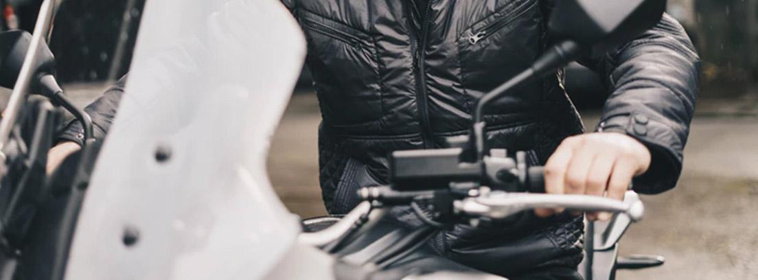 Hombre con barba montado en moto y mirando hacia espejo retrovisor.