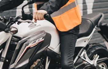 Persona montada sobre moto con los pies sobre el suelo.