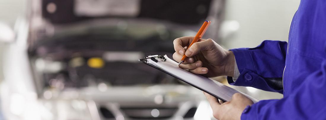Mecánico apuntando en una libreta con un coche al fondo