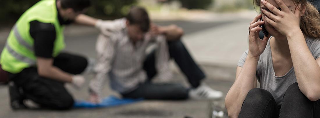Persona tapándose la cara con la mano y sentada en el suelo.