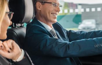 Hombre y mujer felices dentro de un coche nuevo