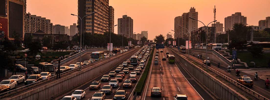 Carretera en ciudad en varias direcciones con coches circulando.