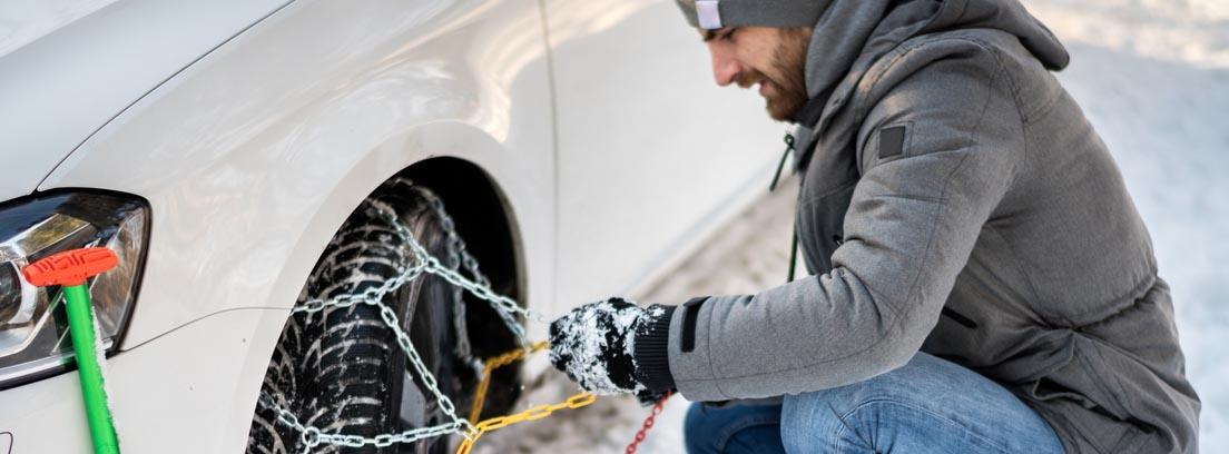 Hombre agachado poniendo las cadenas de nieve a su vehículo