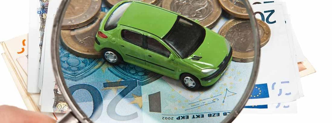 Lupa sobre un coche de juguete verde y billetes y monedas de euro