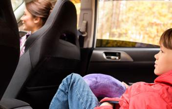 Niño tumbado en el asiento trasero de un coche