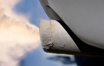 Humo blanco saliendo de un tubo de escape de un coche, uno de los síntomas de la retroalimentación en los motores diésel