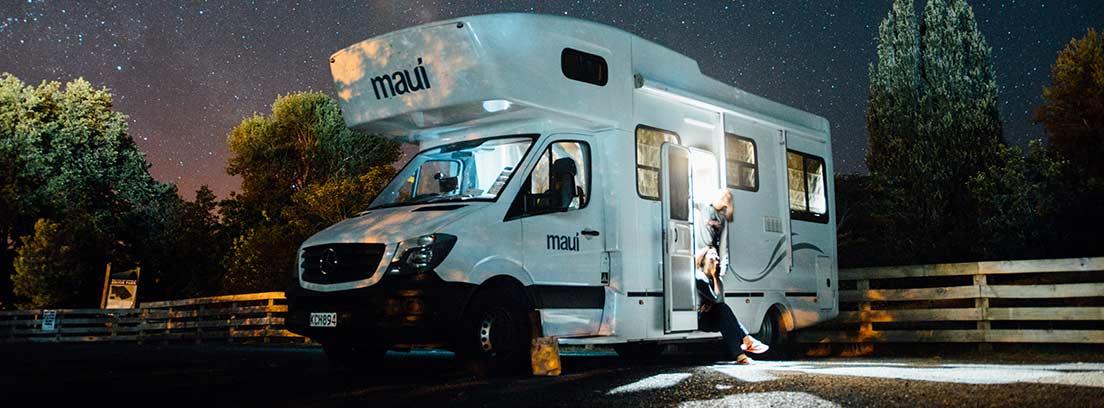 Autocarvana aparcada en el campo por la noche con una persona en la puerta