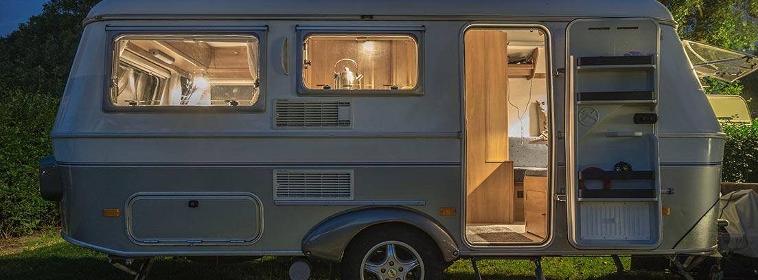 Caravana aparcada con las luces interiores encendidas y puerta abierta