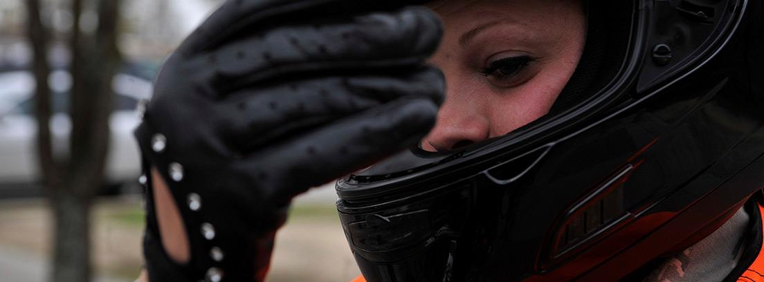 Mujer colocándose unos guantes para moto