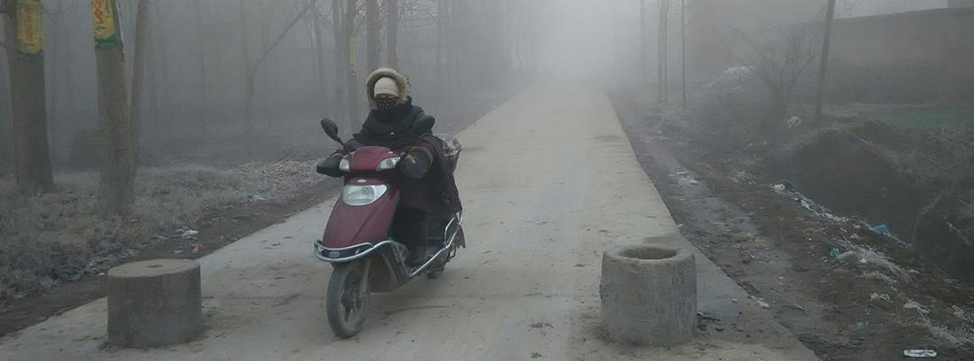 Hombre abrigado circulando con una moto en la niebla