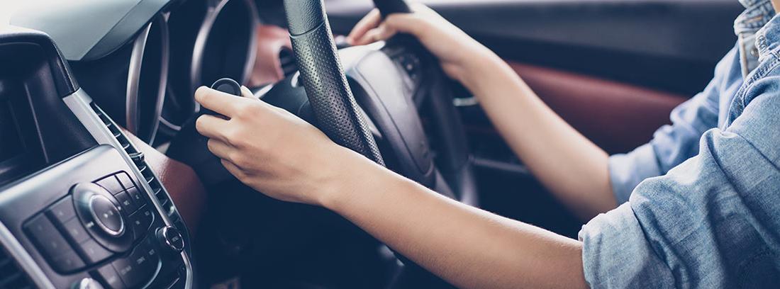 Interior de un coche con una mujer con las manos en el volante conduciendo a la derecha