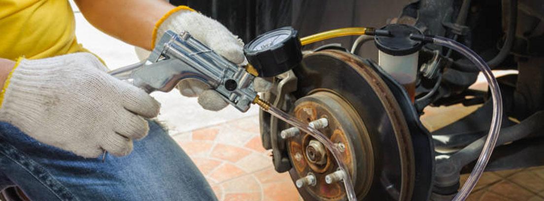 Persona de rodillas junto a rueda coche con tubo conectado al purgador.