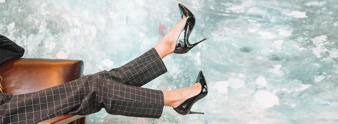 Pies con zapatos de tacón altos y finos negros en el aire.