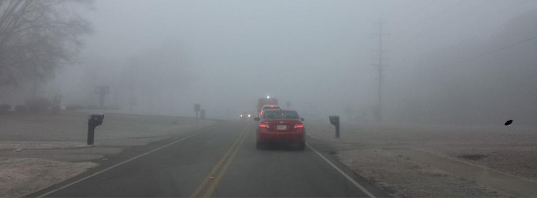 Coches circulando por una carretera con niebla