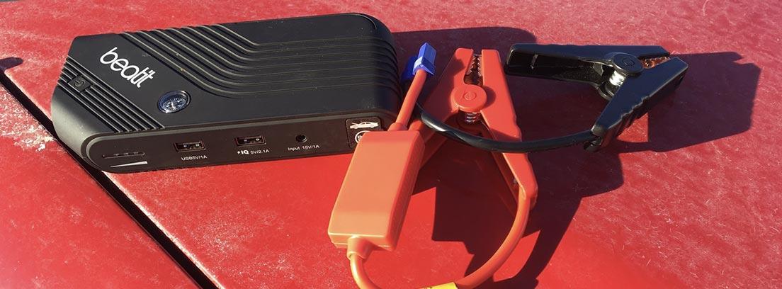 Arrancador de baterías portátil con pinzas sobre el capó de un camión