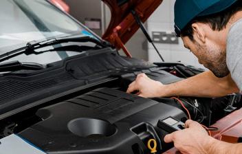 Hombre usando un voltímetro para comprobar el voltaje de la batería de un coche