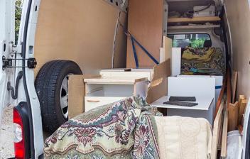 Interior de furgoneta con cosas cargadas y revestimiento de madera