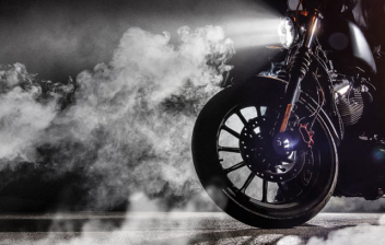 Motorista sobre una moto en una nube de humo o niebla