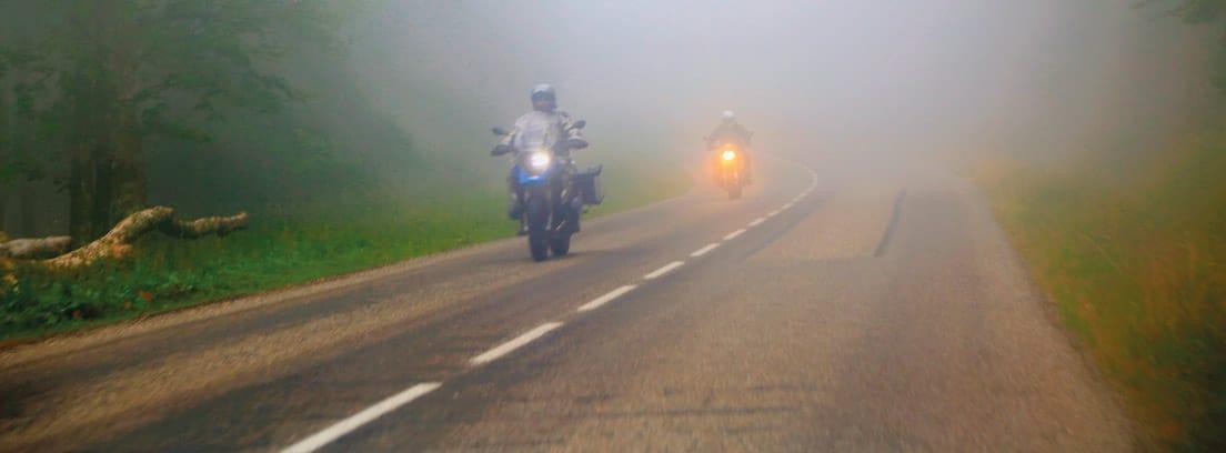 Dos motos circulando en una carretera bajo la niebla