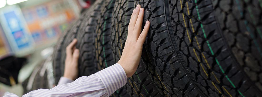 Hombre poniendo las manos sobre unos neumáticos en un expositor