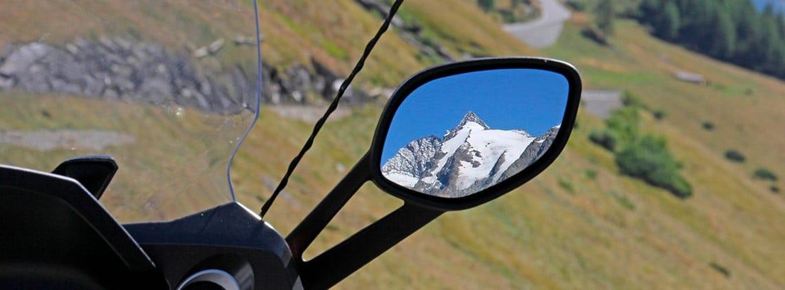 Retrovisor derecho de una moto en el que se refleja una montaña nevada