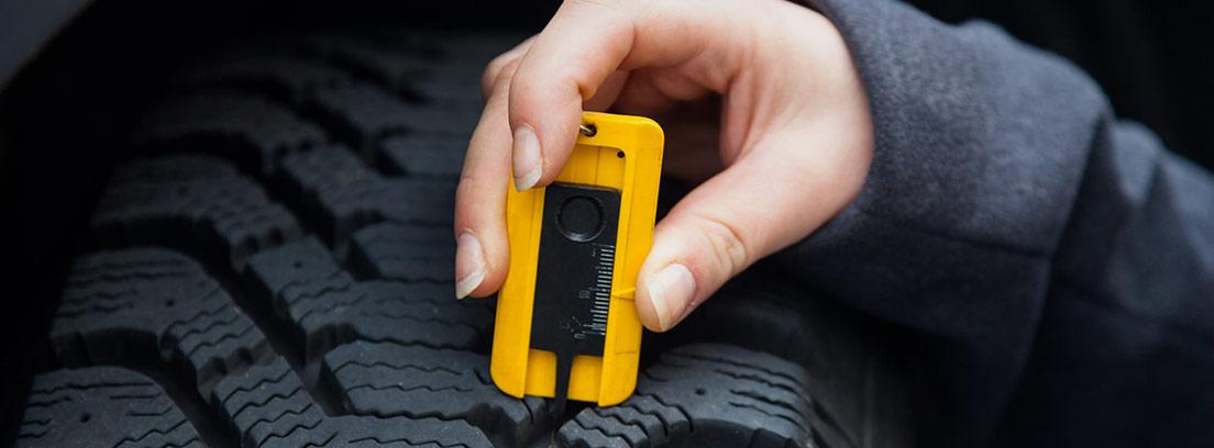 Mano midiendo la marca de rodadura de neumático