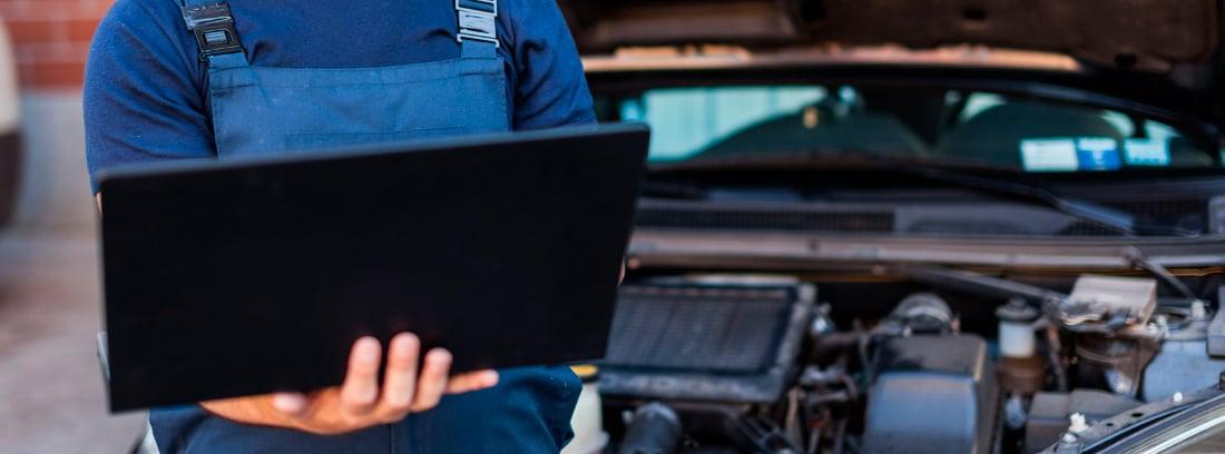 Mecánico con un ordenador junto a un coche con el capó abierto