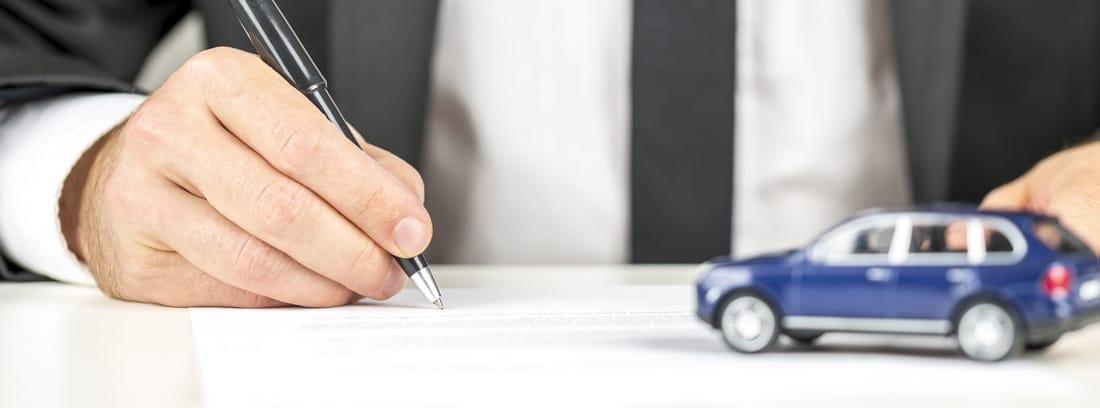 Hombre firmando un papel con un coche de juguete al lado