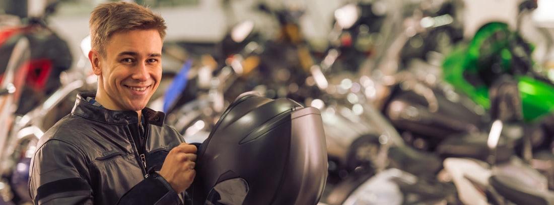 Chico sonriente colocándose el casco de la moto