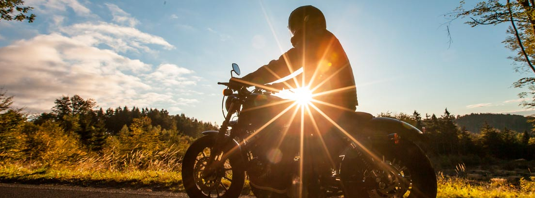 Moto y motorista de perfil en una carretera de montaña con el sol al fondo