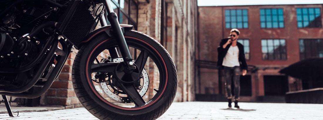 Vista parcial de una moto y hombre acercándose a ella