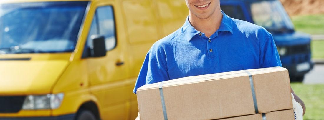 Hombre sujetando cajas con furgoneta al fondo