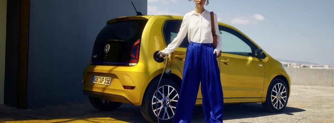 Volkswagen E-Up 2020 de color amarillo siendo recargado por una mujer