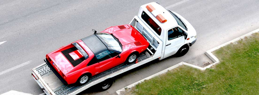 Grúa transportando un coche rojo
